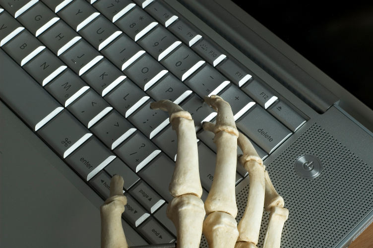 The boney hands of a skeleton type on a computer keyboard